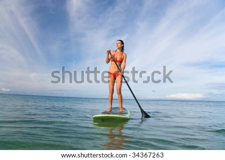 beautiful stand up paddle girl on turquoise waters exercising - stock photo