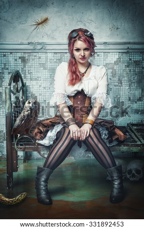 Beautiful steampunk witch sitting in the abandoned room - stock photo