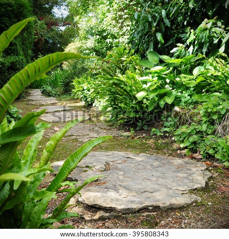 Beautiful Stepping Stone Path through a Green Leafy Garden - stock photo