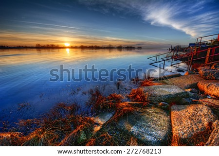 Beautiful stones and colorful grass along a riverbank with distant trees at sunset - stock photo