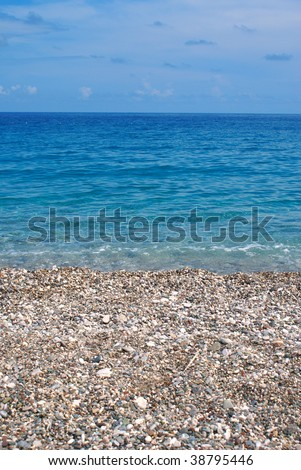 Beautiful stony beach against blue sky and crystal blue water - stock photo
