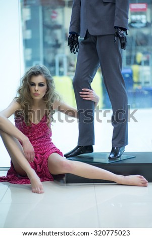 Beautiful straight slim young sensual blonde woman model with bright makeup and curly hair in red dress sitting barefoot near mannequin in grey suit on shop background, vertical - stock photo