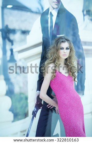 Beautiful straight slim young sensual blonde woman model with bright makeup and curly hair in red dress standing near mannequin in grey suit on shop background, vertical picture - stock photo