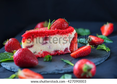 beautiful strawberry cake, mint and strawberries on a plate of slate, black background - stock photo