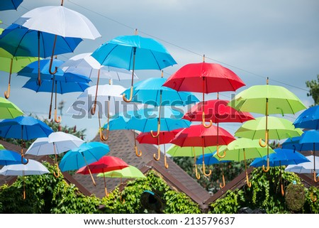 Beautiful street with many green trees on it decorated with nice colored umbrellas hanging over the roofs of nice houses - stock photo