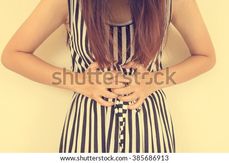 Beautiful stressed business woman suffering from pain in stomach. Vintage closeup portrait - stock photo