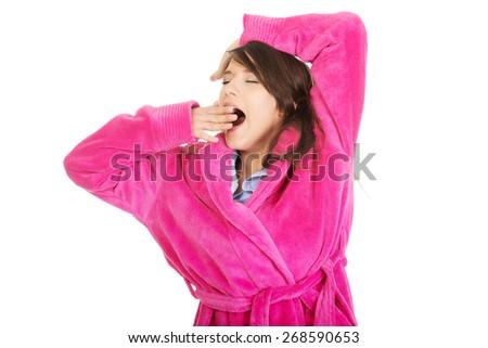Beautiful stretching and yawning woman wearing pink bathrobe. - stock photo