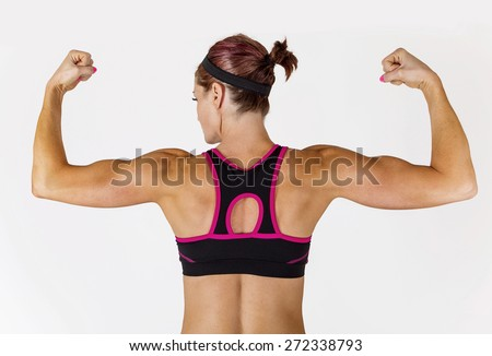 Beautiful strong muscular woman flexing her biceps and arm muscles. View from behind to show her ripped back and arms. - stock photo