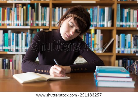 Beautiful student girl studying in college library. Writing notes at her notebook. Selective focus on face.  - stock photo