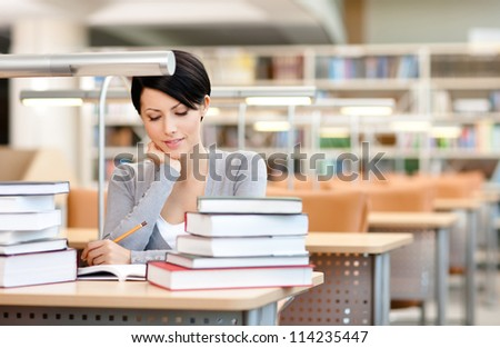 Beautiful student studies with piles of books at the reading hall - stock photo