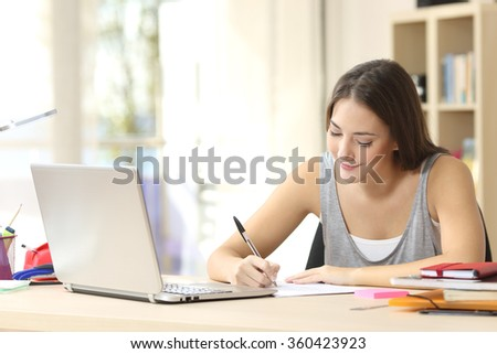 Beautiful student studying on line and learning writing notes in a desk at home - stock photo
