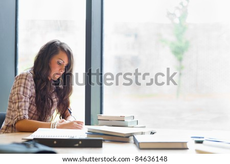 Beautiful student writing an essay in a library - stock photo