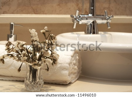 Beautiful stylish bathroom interior with white folded towel, white sink, bottle of liquid soap and some dry flowers - stock photo