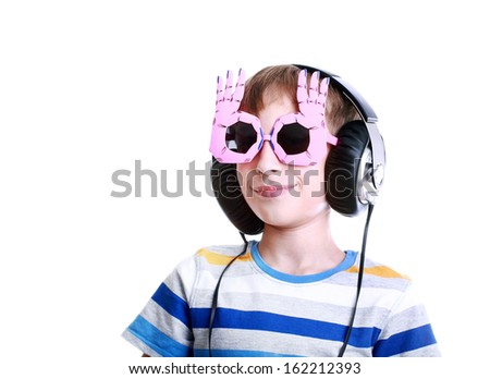 Beautiful stylish blond boy in colorful t-shirt with wearing big professional headphones listening to music and smiling  (music concept) - stock photo