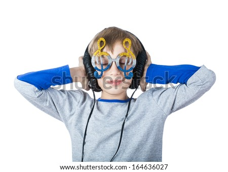 Beautiful stylish blond child wearing big professional headphones and funny glasses  listens to music with his eyes closed  - stock photo