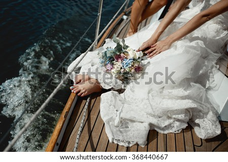 Beautiful stylish bride with a bouquet of hydrangeas and roses in the luxurious lace white dress on  yacht  board at sea - stock photo