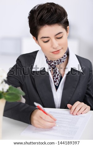 Beautiful stylish female receptionist completing a form on top pf a counter while assisting a client - stock photo