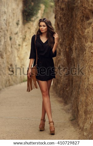 Beautiful stylish girl wearing black dress and sunglasses with long sexy legs walking on a path at nature between rocks - stock photo
