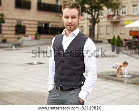 Beautiful stylish man against old European city. - stock photo