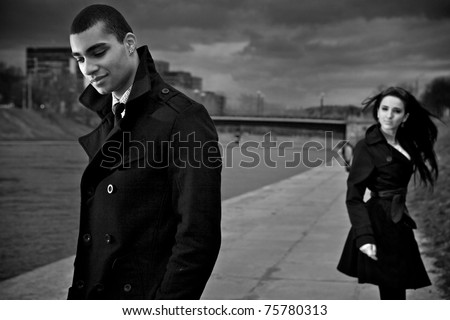 Beautiful stylish pair of young people outdoor going in different directions. Close-up men face. - stock photo