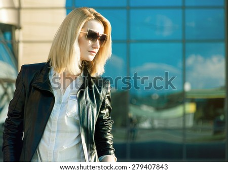 Beautiful stylish woman in trendy sunglasses and leather jacket over sopping mall. - stock photo