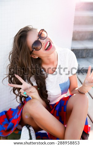 Beautiful stylish young fashion girl with perfect evening make-up with pink lips and green eyes,staying near white pool in elegant summer clothes hills,skirt,top and jacket, and golden bijou.laughing - stock photo