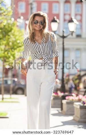Beautiful stylish young woman on a street - stock photo
