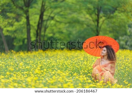 Beautiful stylish young woman with curly hair holding a colorful orange parasol in a meadow filled with yellow summer flowers as she clasps a chiffon scarf around her shoulders and looks to the side - stock photo