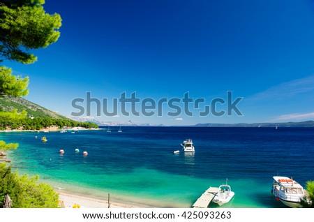 Beautiful Summer Adriatic Sea coastline view with pine tree yachts and boats, island Brac, Croatia. turquoise bay - stock photo