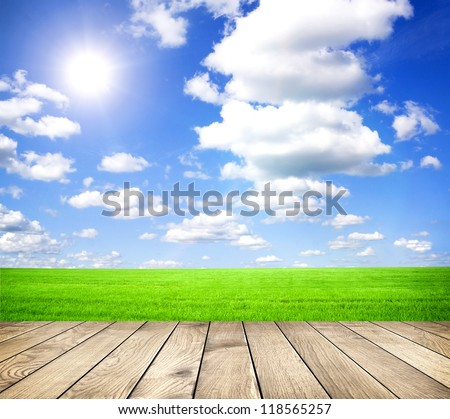 Beautiful summer green field with blue sky with grey clouds and bright sun and wooden planks on floor - stock photo
