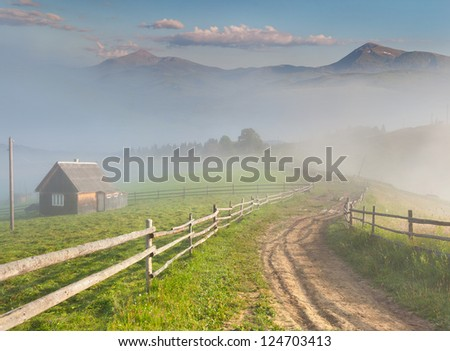 Beautiful summer landscape in a mountain village. Foggy morning - stock photo