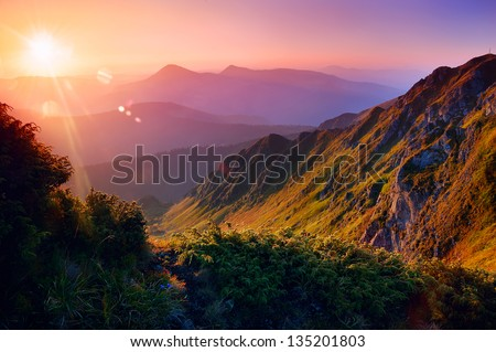Beautiful summer landscape in the mountains with the sun at dawn - stock photo