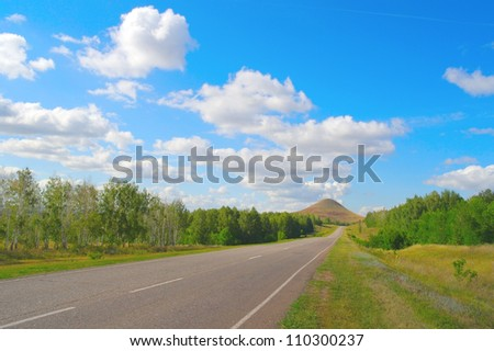 Beautiful summer landscape, road to high mountain. Blue sky with clouds - stock photo