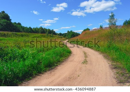 Beautiful summer landscape with road, sky, clouds, grass and trees - stock photo