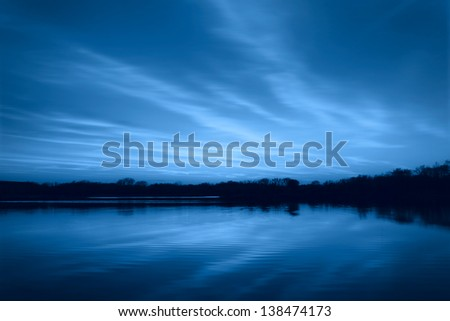 Beautiful summer sunset on the lake with a blue filter - stock photo