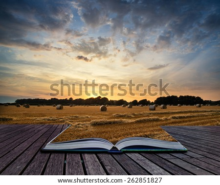 Beautiful Summer sunset over field of hay bales in countryside landscape conceptual book image - stock photo