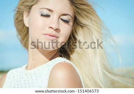 Beautiful summer woman posing outdoors healthy girl at vacation on background of blue sky. Attractive happy blonde woman resting. Summer makeup hairstyle. long hair perfect skin. Romantic. - stock photo