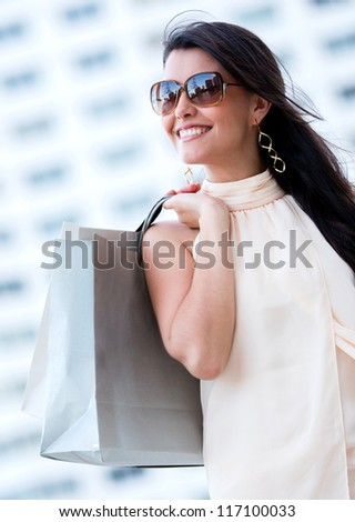 Beautiful summery shopping woman holding bags and smiling - stock photo