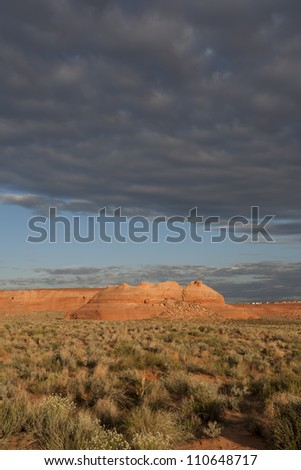 Beautiful sun kissed landscape image of stone formations in Page Arizona on a beautiful day with storm clouds overhead. - stock photo