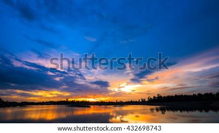 Beautiful sun set over lake with blue sky - stock photo