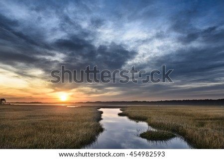 Beautiful Sunrise Along Coastal Inlet with Dramatic Clouds - stock photo