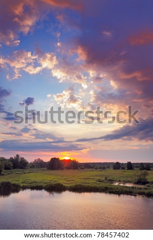 Beautiful sunrise and romantic clouds on the sky. Flood waters of Narew river, Poland. - stock photo