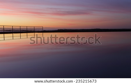 Beautiful sunrise and tranquil reflections at Wombarra.  Stand still in quietude  while natures stunning beauty envelops you and purifies the soul purging your mind of inner stresses and turmoil.  - stock photo