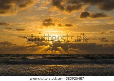 Beautiful sunrise cloudscape over ocean background. Sun rays beaming through picturesque clouds above sea - stock photo