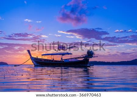 Beautiful sunrise in Rawai Phuket island Thailand with Long tailed boat Ruea Hang Yao - stock photo