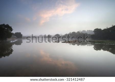 Beautiful sunrise landscape over misty lake in Summer - stock photo