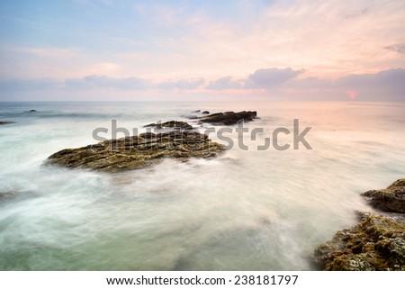 Beautiful sunrise landscape seascape over rocky coastline.  - stock photo