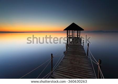 Beautiful sunrise of wooden landing with pavilion in the sea at Black Sand Beach, Trat Province of Thailand - stock photo