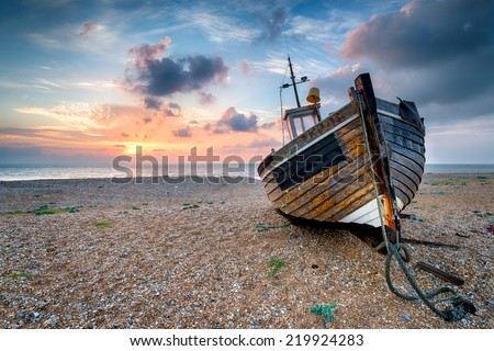 Beautiful sunrise over an old wooden fishing boat on a pebble beach - stock photo