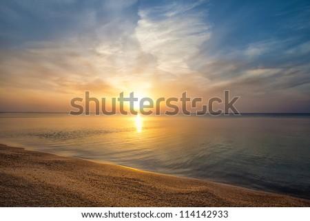 Beautiful sunrise over beach - stock photo